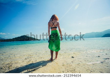 A slim young woman wearing a colorful sarong is standing on a tropical beach - stock photo