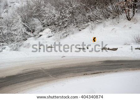 A slippery and curvy road in the winter - stock photo
