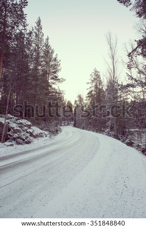 A slippery and curvy road in the winter. Image taken in Finland during sunrise on a cold morning. First snow is covering up the road and forest. Image has a vintage effect applied. - stock photo