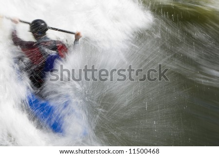 A slow shutter speed shot of a kayaker in very rough whitewater. Shot with copyspace on the right hand side of the frame.