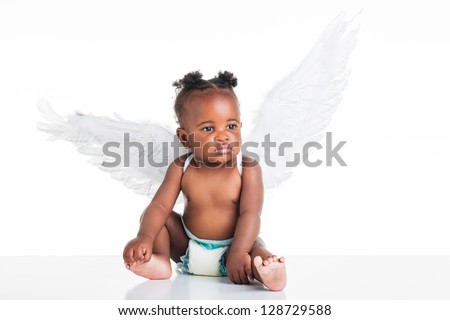 A small African baby with her angel wings on the back and a nappy on. - stock photo