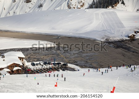 A small airplane landing on the short runway of the altitude airport of Courchevel, an exclusive ski resort in France, Europe. - stock photo