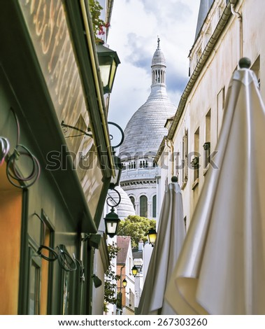 A small alley in Montmartre with the church of Sacre Coeur in background, Paris, France - stock photo