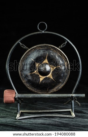 a small asian gong over a dark background - stock photo