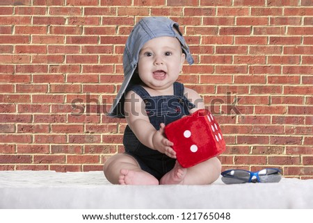 a small baby with his cap and a dice