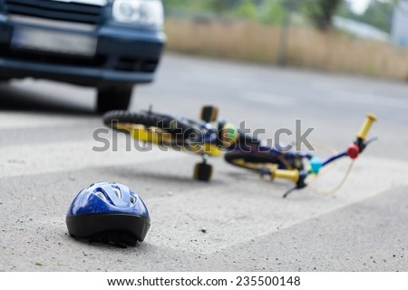 A small bike and a helmet lying on the road - stock photo