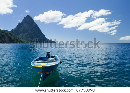 A small blue boat on a beach in St Lucia with Petit Piton in the background - stock photo