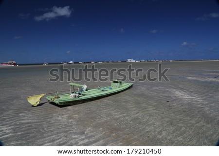 A small boat at the brazilian beach coast Porto de Galinhas, Pernambuco - Brazil. - stock photo
