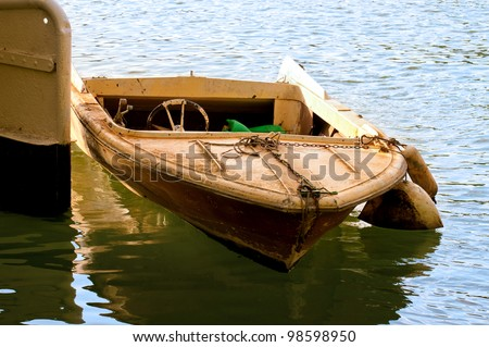a small boat moored in water - stock photo