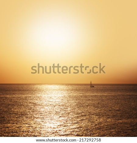A small boat sailing on the sea at sunset - stock photo