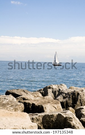 A small boat sailing on the water on a clear day. - stock photo