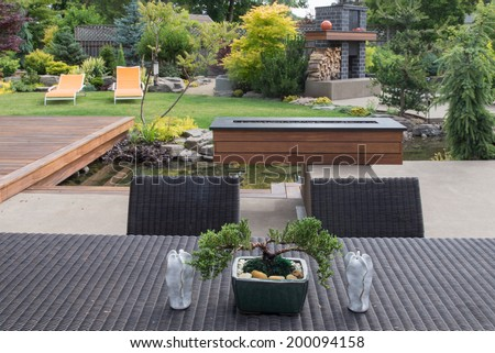 A small bonsai sits on a contemporary backyard patio table between two sculptured candles with a beautifully landscaped yard in the background.   - stock photo