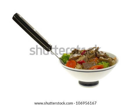 A small bowl filled with beef teriyaki and vegetables on rice with fork on a white background.