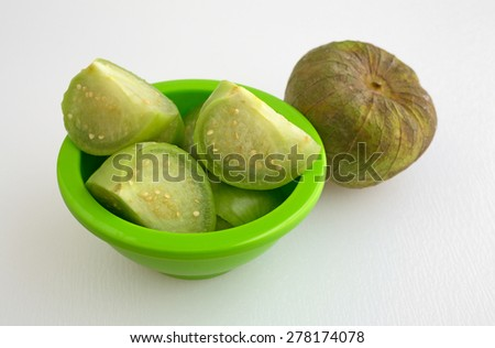 A small bowl filled with chopped tomatillos plus a whole tomatillos on a white cutting board. - stock photo