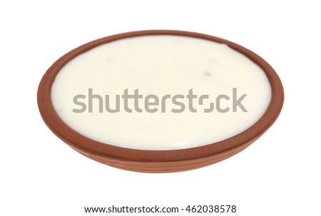A small bowl filled with fat-free blue cheese dressing on a white background.