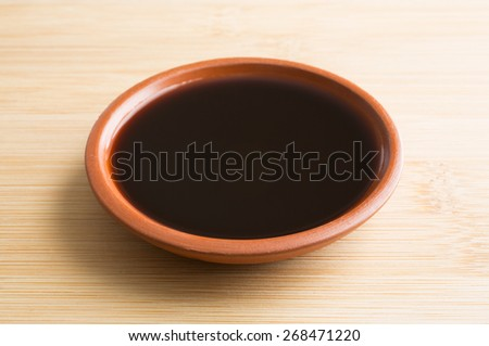 A small bowl filled with mesquite flavored liquid seasoning for cooking and barbecuing on a wood cutting board. - stock photo