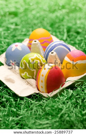 A small box of easter eggs on artificial gras - stock photo