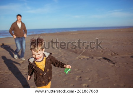 A small boy and his dad are running on the sand in a sunny day and flying a kite. Clothes: casual. - stock photo