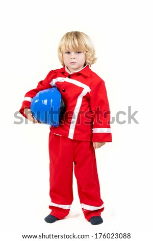 A small boy in red holds a hard hat.