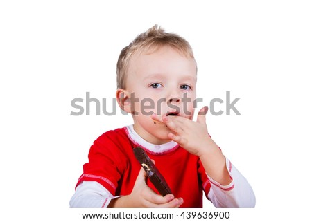 A small boy in red shirt eating whole bar of chocolate. Isolated on white background