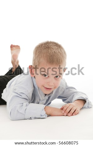 A small boy in the studio, dressed up in a suit and pretending to be a businessman, lying down.