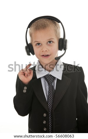 A small boy in the studio, dressed up in a suit and pretending to be a businessman, talking on a headset. Isolated on white. - stock photo