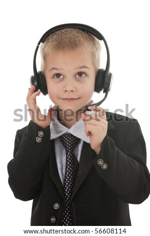 A small boy in the studio, dressed up in a suit and pretending to be a businessman, talking on a headset. Isolated on white.
