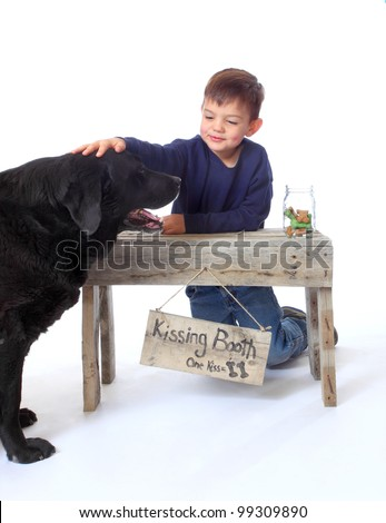 A small boy pets  a black lab at a doggy kissing booth. - stock photo