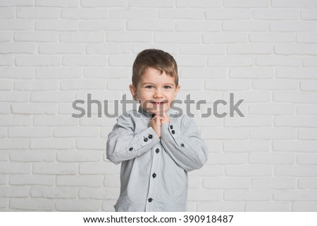 A small boy playing on white background. Cute baby smiles and keeps his hands together.