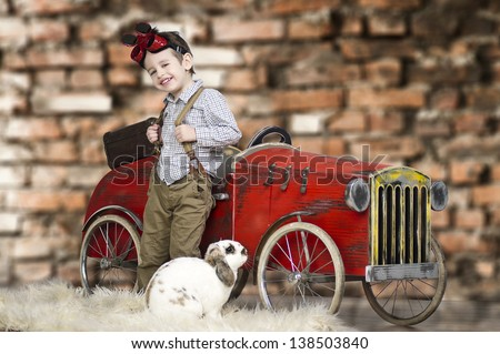 A small boy playing with rabbit   - stock photo
