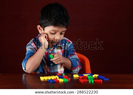A small boy plays with toy alphabets in a dark background - stock photo