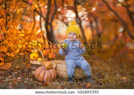 A small boy sits in yellow cap on a wicker pufe in the autumn forest with pumpkins and apples and smiling