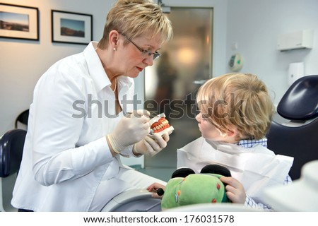 A small boy sitting in a chair and a dentist.