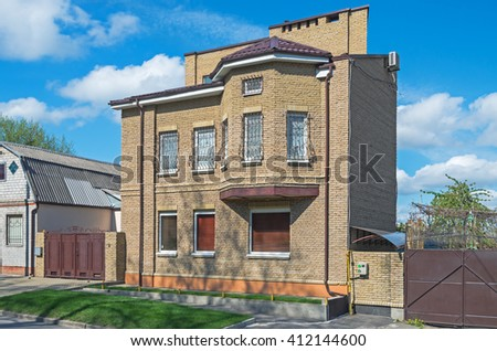 A small brick house covered with a red metal tile - stock photo