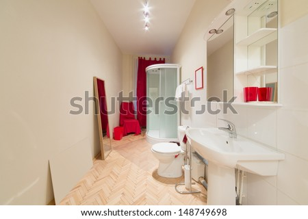 A small bright bathroom with a shower cabin, sink and toilet bowl
