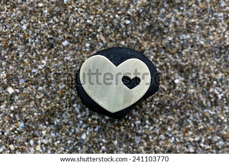 A small bright metallic heart shape is placed on a black stone on dark sand background. - stock photo
