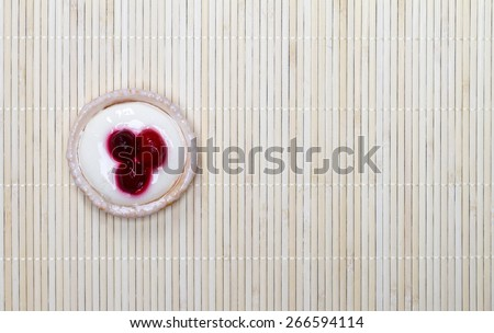 A small cake with strawberries on beige bamboo mat background - stock photo
