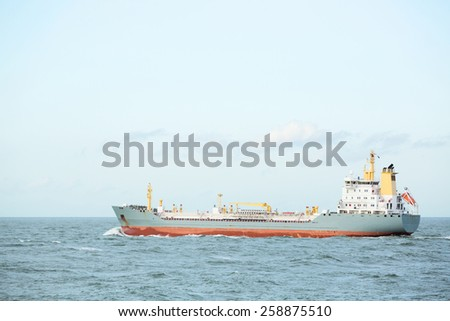 A small cargo ship in open water with clear sky.