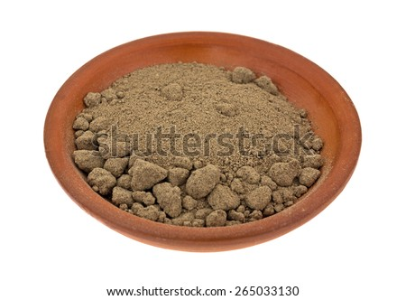 A small ceramic bowl containing comfrey root powder on a white background. - stock photo