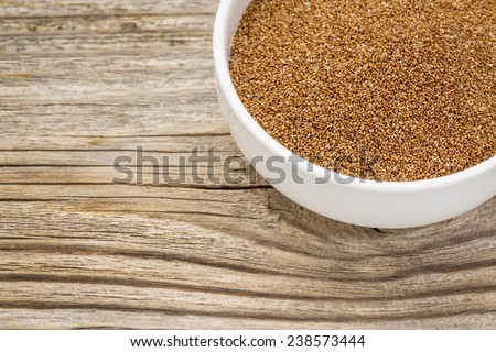 a small ceramic bowl of gluten free teff grain against weathered wood background - stock photo
