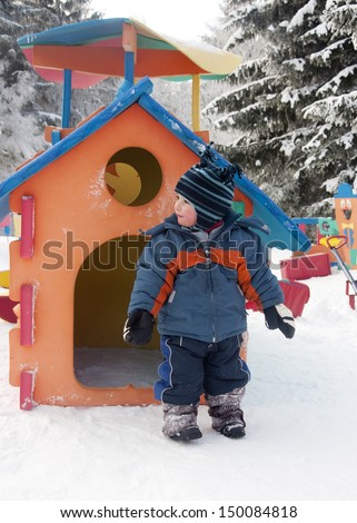 A small child, boy or girl, in a temporary winter snow playground in a ski resort.
