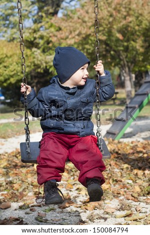 A small child, boy, playing on a swing in a playground in the autumn or fall. - stock photo