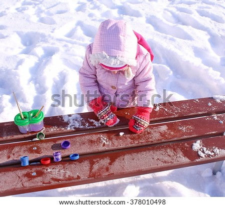 A small child draws gouache on snow