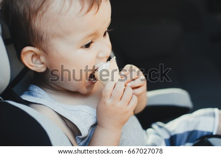 A small child eating ice cream, sitting strapped in the car seat