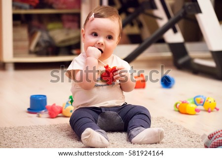 A small child, infant, plays with a rubber doll toys, chews it, teething