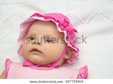 a small child is lying and smiling on white