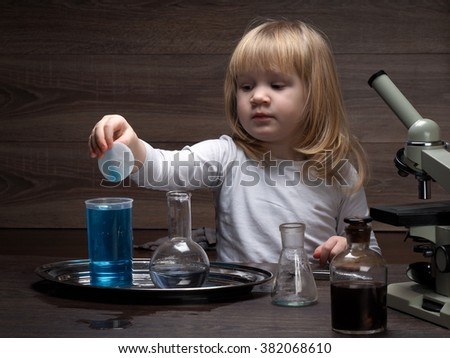 A small child learns to work with tweezers. Conduct chemical experiments. Chemical vessels. Home Laboratory. Multi-colored liquid. Microscope