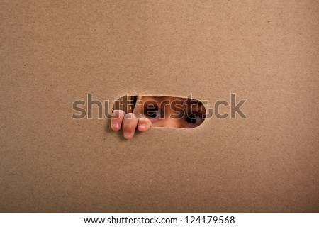 A small child looking out the gap of craft box - stock photo