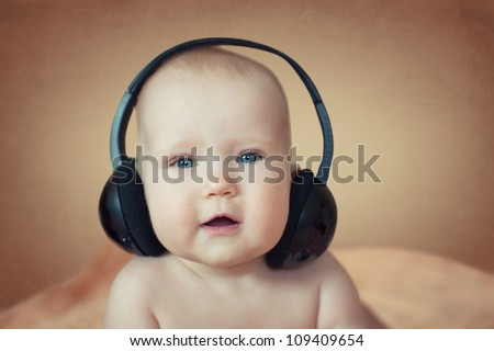 a small child playing with headphones - stock photo