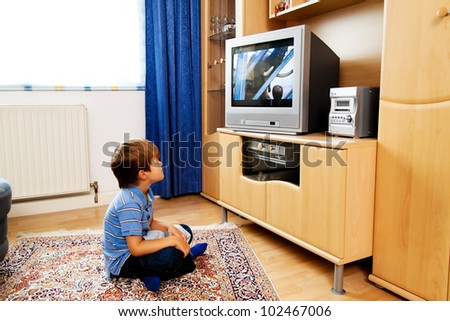 a small child watching television with tv